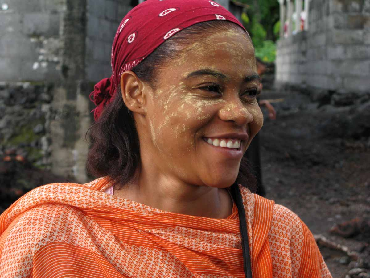 "Comorian woman using ""bwe la mssitzanou,"" a stone ground sandal wood powder, as a facial cosmetic. 