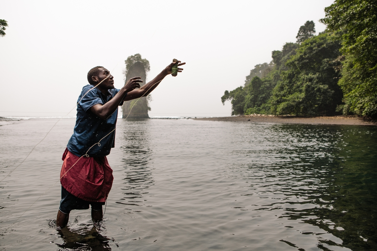 Photo © Tristan Spinski | Amancio Ammoet Motove Etingüe, a fourth year student at UNGE School of Environmental Studies in Equatorial Guinea, fishes in a stream on the beach near his hometown of Ureca on Bioko Island in Equatorial Guinea.